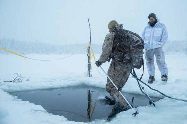 A U.S. Marine with Marine Rotational Force-Europe 19.1 jumps in freezing water during an ice-breaking drill as part of Exercise White Ulfberht in Setermoen, Norway, Jan. 22. (Cpl. Nghia Tran/Marine Corps)
