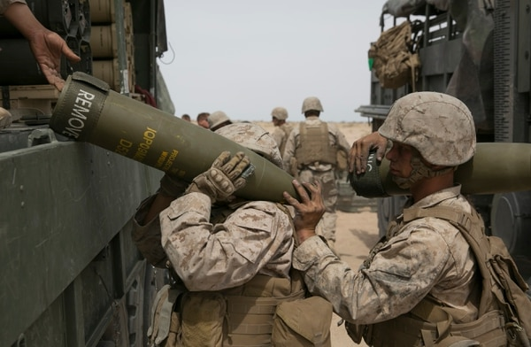 Cpl. Caroline Ortiz, a Marine with the Ground Combat Element Integrated Task Force, gets a hand with lifting a shell during an artillery assessment at Marine Corps Air Ground Combat Center Twentynine Palms in Twentynine Palms, Calif., on Friday, April 10, 2015. In addition to artillery, the GCEITF is also evaluating the integration of female Marines into infantry and mechanized MOS's. (Mike Morones/Staff)