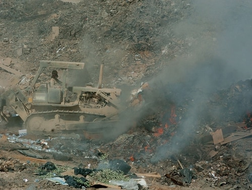 A soldier uses a bulldozer to maneuver refuse into a burn pit at Balad, Iraq, in 2004. (DoD)