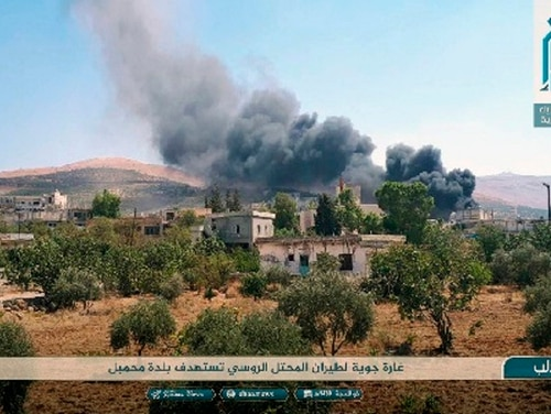 This photo released Tuesday, Sept 4, 2018, by the al-Qaida-affiliated Ibaa News Agency shows smoke rising over buildings that were hit by airstrikes in Mahambal village, in the northern province of Idlib, Syria. The Arabic text reads,