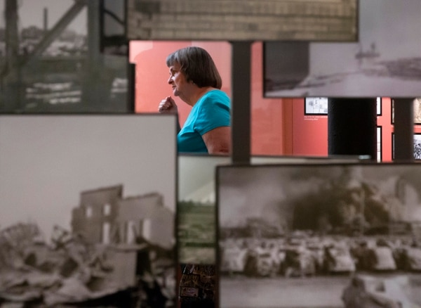 Texas City disaster survivor Barbara Girardin-Klaver walks among photographs documenting the 1947 explosions while visiting the Texas City Museum on Saturday. (Stuart Villanueva/The Galveston County Daily News via AP)