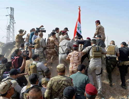 Iraq's Prime Minister Haider al-Abadi, directly beneath flag, and others raise the national flag at a border crossing with Syria days after Iraqi forces retook it from the Islamic State group, in Qaim, Iraq, Sunday, Nov. 5, 2017. (Osama Sami/AP)