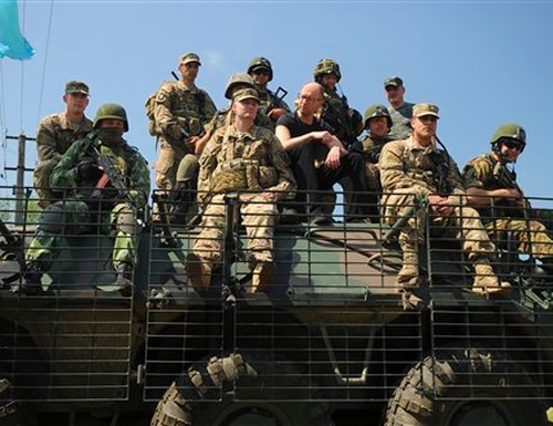 Ukraine's Prime Minister Arseniy Yatsenyuk, center, surrounded by the US and Ukrainian soldiers atop an armored personnel carrier as they observe joint training exercises on the military base in the Lviv region, western Ukraine, Wednesday, June 3, 2015. Troops from the United States and Ukraine conduct joint training exercises intended to help bolster Ukraine's defense against incursions from Russian-backed separatists. (AP Photo/Andrew Kravchenko, Pool)