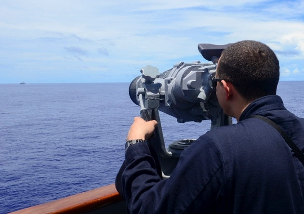 Ensign Matt Delavega, from Grass Valley, Calif., uses a set of high-powered binoculars to observe a Chinese navy vessel from the bridge of the Arleigh Burke-class guided-missile destroyer USS Sterett (DDG 104). Sterett is underway in the U.S. 7th Fleet area of responsibility as part of the Carl Vinson Carrier Strike Group. Carl Vinson and its embarked air wing, Carrier Air Wing 17, are on deployment in the U.S. 7th Fleet area of operations supporting Valiant Shield. Valiant Shield is a U.S.-only biennial exercise in which participation will focus on the integration of joint training among U.S. forces. (U.S. Navy photo by Mass Communication Specialist 3rd Class Eric Coffer/Released)