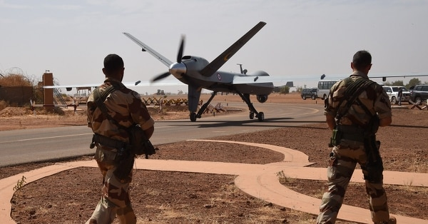 French soldiers pass a Reaper drone about to take off from the military airport Diori Hamani in Niamey, Niger. (Dominique Faget/AFP/Getty Images)