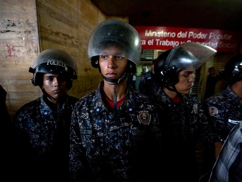 Venezuelan Bolivarian National Police guard the Labor Ministry while workers protest outside the building in Caracas, Venezuela. President Donald Trump has discussed military options for a coup in the country.(Fernando Llano/AP)