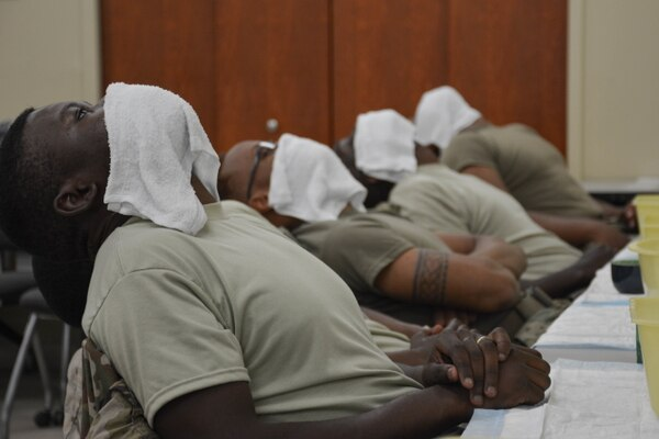 Soldiers assigned to the 3rd Infantry Division Sustainment Brigade use hot towels to warm their faces during a shaving clinic in 2017 at the brigade's organizational classroom. The hot towels help stimulate the skin to bring out any oils and sweat that can be used for a lubrication layer between the skin and the razor. The majority of sailors affected by a new Navy shaving policy will be African-American men. (Army)