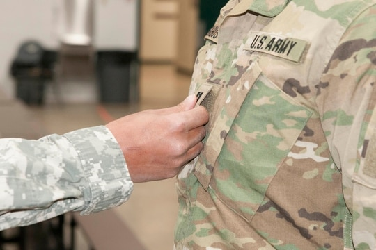 A soldier is promoted to his newly appointed rank by attaching the insignia to his uniform with friends and colleagues present. (Army)