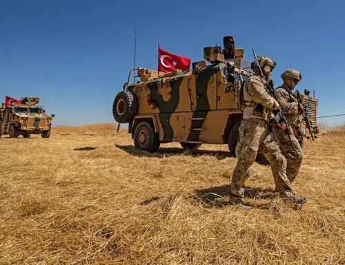 U.S. troops walk past a Turkish military vehicle during a joint patrol with Turkish troops in the Syrian village of al-Hashisha on the outskirts of Tal Abyad town along the border with Turkish troops, on Sept. 8, 2019. (Delil Souleiman/AFP via Getty Images)