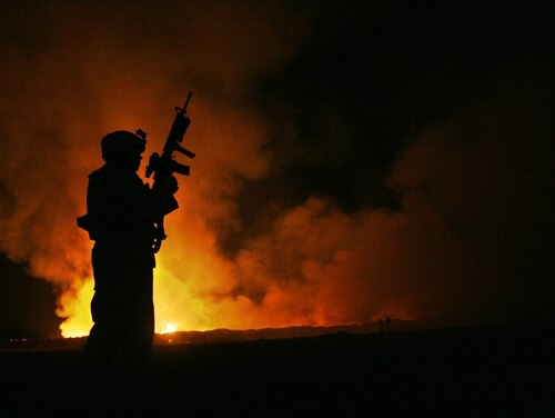 A Marine stands guard as smoke and flames rise from a burn pit at Camp Fallujah in Iraq on May 25, 2007. Advocates say that not enough is being done by federal officials to address the long-term health problems from exposure to the pits. (Cpl. Samuel D. Corum/Marine Corps)