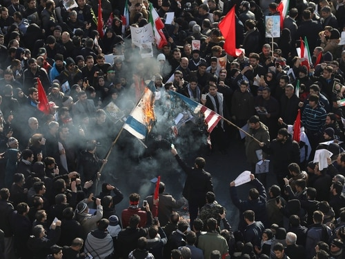 Mourners in Tehran burn mock flags of the U.S. and Israel during a funeral ceremony for Iranian Gen. Qassem Soleimani and his comrades on Monday. (Ebrahim Noroozi/AP)