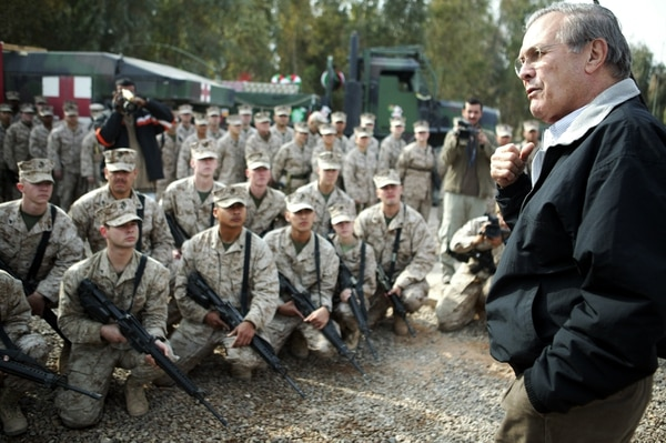 In this photo released by the US Marines, U.S. Defense Secretary Donald H. Rumsfeld, on a surprise Christmas Eve visit talks to Marines and Sailors of Bravo Surgical Company, 1st Medical Battalion,1st Force Service Support Group, I Marine Expeditionary Force, at their base in Fallujah, Iraq, Friday Dec. 24 2004. (AP Photo/USMC, Cpl. K.T. Tran )