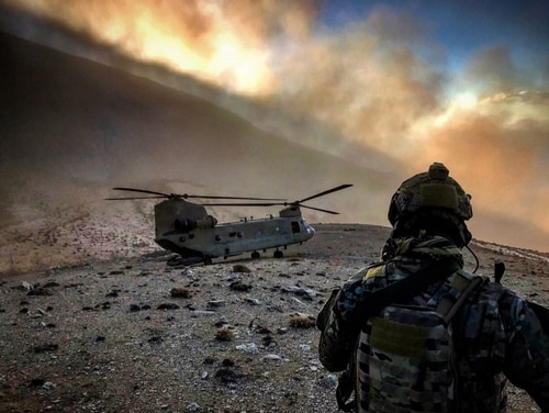An 83rd Expeditionary Rescue Squadron airman observes a U.S. Army CH-47 Chinook at an undisclosed location in Afghanistan. (Air Force)