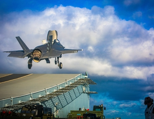 A Marine with Marine Fighter Attack Squadron (VMFA) 211 launches an F-35B Lightning II Joint Strike Fighter from the deck aboard Her Majesty's Ship (HMS) Queen Elizabeth at sea on 10 October, 2020. (1st Lt. Zachary Bodner/Marine Corps)