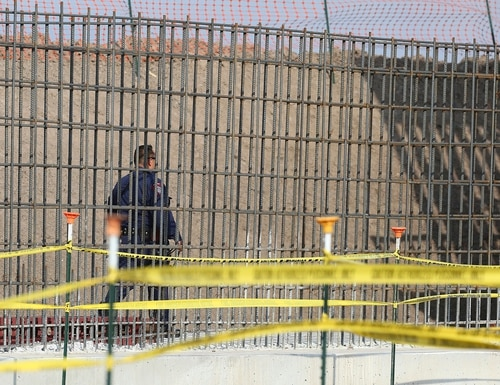A McAllen K-9 police officer walks past rebar that will make up the border wall before DHS Acting Homeland Secretary Chad Wolf tours and speaks to the local media at the border wall under construction on Thursday, Nov. 21, 2019, south of Donna, Texas. (The Monitor via AP)