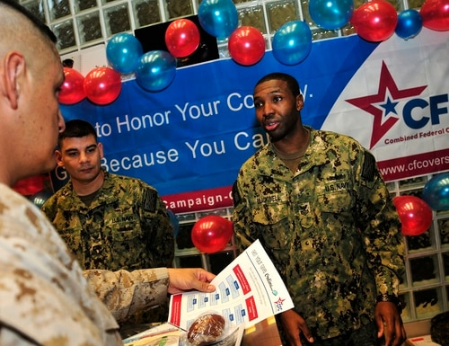 Sailors hand out information in Bahrain in 2013 during a kickoff event for the Combined Federal Campaign-Overseas. The CFC is an annual event that coordinates fundraising efforts by federal employees for charitable organizations. (U.S. Navy photo by Mass Communication Specialist 1st Class Felicito Rustique)