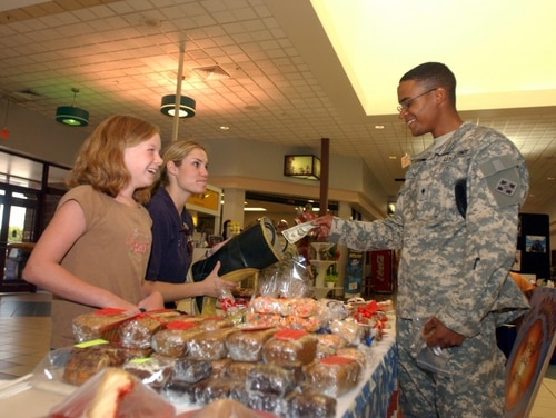 Spc. Andrew Naef, fire support specialist, Headquarters and Headquarters Troop, 3rd Brigade Combat Team, 4th Infantry Division, donates to the boot for the Fort Carson Firefighter Bake Sale. Heather Fox, center, student firefighter, and Emily Robinette, 10, staff the table at the Post Exchange. The bake sale raised more than $2,000 for the Fort Carson Firefighter Association largely due to donations from Soldiers and the Fort Carson community. (Photo Credit: Spc. Paul Harris)