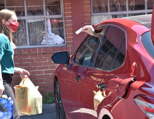 A staff member at the Fort Bragg, N.C., branch of the Armed Services YMCA takes bags of food to a military family's car in the spring of 2020. (Armed Services YMCA)