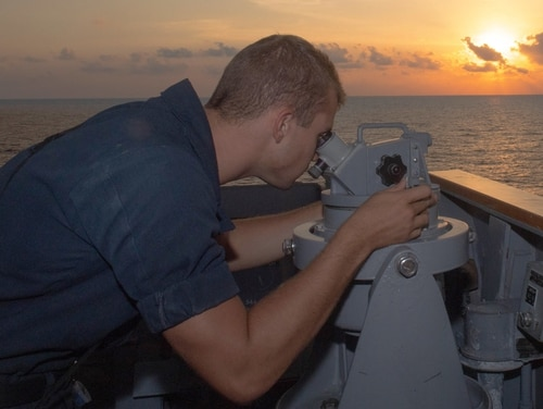 Seaman Derek Mischo uses an alidade to search for ship contacts on board the guided-missile cruiser Antietam on July 20 in the South China Sea. (Mass Communication Specialist 1st Class Alexandra Seeley/Navy)