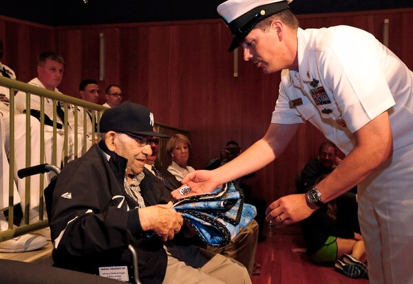 Baseball Hall of Famer Yogi Berra is presented with a quilt and a medal by Cmdr. Jim Wallace during a D-Day presentation at the Yogi Berra Museum in Montclair, N.J., on June 6, 2014. Berra served in the Navy as part of the D-Day invasion. (Rich Schultz/AP)