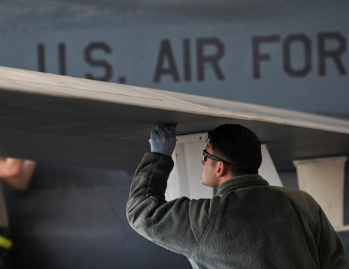 Airman 1st Class Christian De Jesus Roman, crew chief with the 380th Expeditionary Aircraft Maintenance Squadron, inspects an RQ-4 Global Hawk in February 2018 on Al Dhafra Air Base in the United Arab Emirates. Air Force officials are taking a hard look at making cuts to legacy weapons systems. (Airman 1st Class Blake Browning/Air Force)