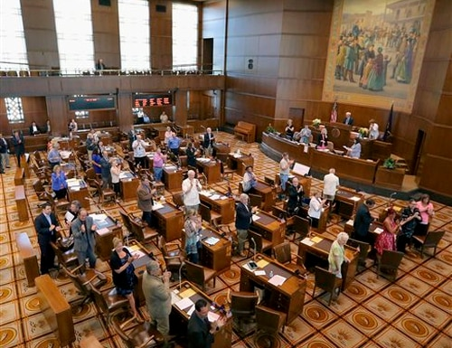 The Senate applauds Monday, July 6, 2015, at the state Capitol in Salem, Ore. Lawmakers pushed Monday to adjourn the 2015 legislative session. (Brent Drinkut/Statesman-Journal via AP) MANDATORY CREDIT