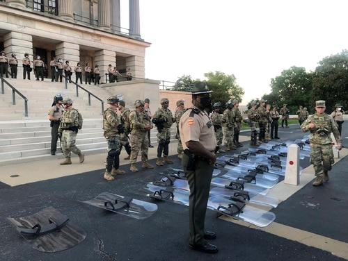 National Guard troops lay down their shields at the request of protesters in Nashville, Tenn., Monday, June 1, 2020. Troops had rushed to get the shields as the crowd walked up the Capitol steps but as the George Floyd vigil participants remained calm, the National Guardsmen granted protesters' request to put the shields down. (Kimberlee Krkuesi/AP)