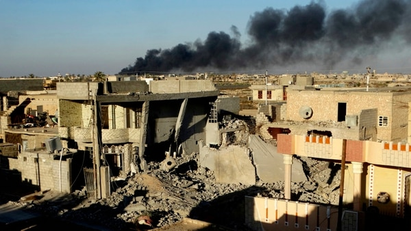 """FILE - Smoke rises from Islamic State group positions after an airstrike by U.S.-led coalition warplanes in the Iraqi city of Ramadi in this Dec. 25, 2015 file photo during the Iraqi government offensive that drove the militants out of the city. Ramadi, the provincial capital of Iraq's Sunni heartland, was declared """"fully liberated"""" early this year. But the cost of victory may have been the city itself, with widespread destruction from strikes, artillery and the militants' scorched earth tactic of destroying buildings and infrastructure as they fled. (AP Photo, File)"""