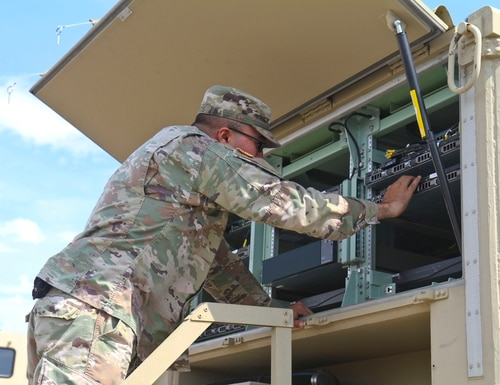 Spc. Francisco Matos checks servers on the Network Operations Security Center installed on a Unit Hub SATCOM truck in preparation for testing the Mission Command Augmentation Support system developed by the 3rd BCT. The system provides connectivity to support network operations regardless of the location or condition of the BCT's tactical operations center. (Staff Sgt. Cody Harding/U.S. Army)