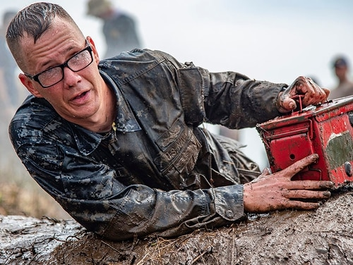 Electronics Technician 1st Class David Hall carries an ammunition box through an obstacle course during a chief petty officer initiation training event. The focus of the obstacle course centered on teamwork and communication. (Chief Mass Communication Specialist Ben Farone/Navy)