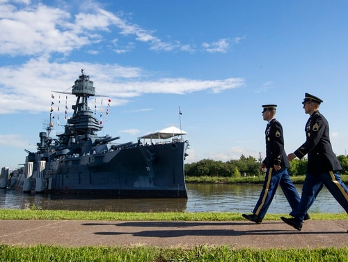 Army Staff Sgt. Jacob Klein, left, and Staff Sgt. Joel Ocasio walk past the museum battleship Texas to participate in a June 6 ceremony commemorating the 75th anniversary of D-Day, in La Porte, Texas. (Brett Coomer/Houston Chronicle via AP)