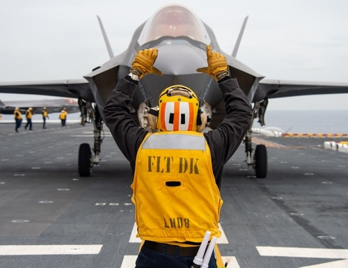 Aviation Boatswain's Mate (Handling) 2nd Class Tyler Randrup directs a U.S. Marine Corps F-35B Lightning II aboard the amphibious assault ship USS Makin Island (LHD 8) on Dec. 3, 2019, in the Pacific Ocean. (Mass Communication Specialist 3rd Class Jacob D. Bergh/Navy)