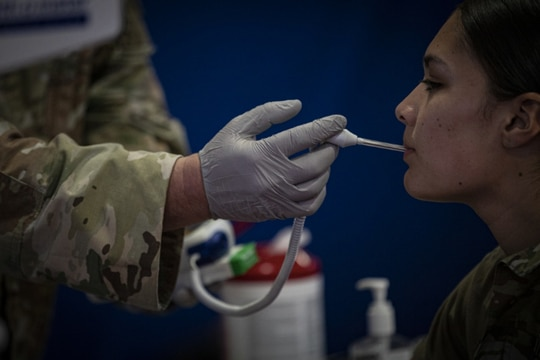 A New Jersey Army National Guard Soldier with the 143rd Transportation Company has her temperature checked during medical screening for state activation at the Teaneck Armory in Teaneck, N.J., on March 19, 2020. (Master Sgt. Matt Hecht/Air National Guard)