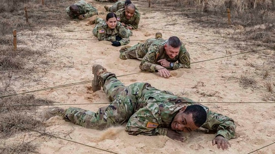 Army Medicine sergeants major low crawl during an obstacle course validation exercise on Fort Gordon, Ga., Jan. 21, 2021, ahead of the Army Best Medic Competition (ABMC). The ABMC will take place from Jan. 25-28 at Fort Gordon. (Spc. Adrian Pacheco/Army)