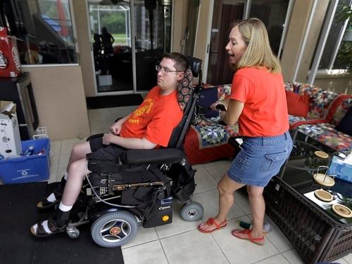 Chris Ott, right, helps maneuver her son, Marine veteran John Thomas Doody, around their family house in September 2013. (Chris O'Meara/AP)