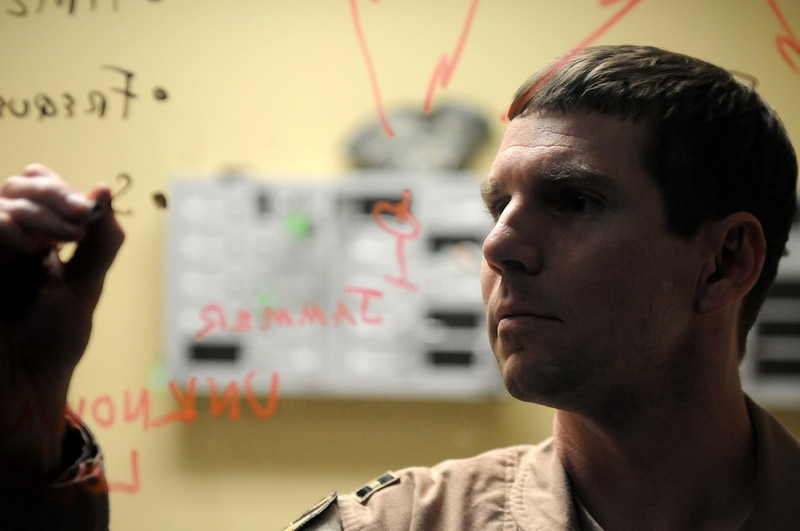 Capt. Brandon Davenport, then-Space Operations Center Combat Operations Division Space Cell chief, diagrams how to geolocate a jamming signal at a deployed location in Southwest Asia, Feb. 28., 2013. (Tech. Sgt. Mike Andriacco/U.S. Air Force)