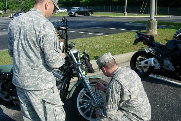 Soldiers inspect a motorcycle using the Tires and Wheels, Cables and Controls, Lights, Oil and Fluids, Chassis, and Sidestand (T-CLOCS) pre-ride checklist. A June 4 memo from the Army secretary got rid of the requirement to do POV checks before holidays and long weekends. (Army)