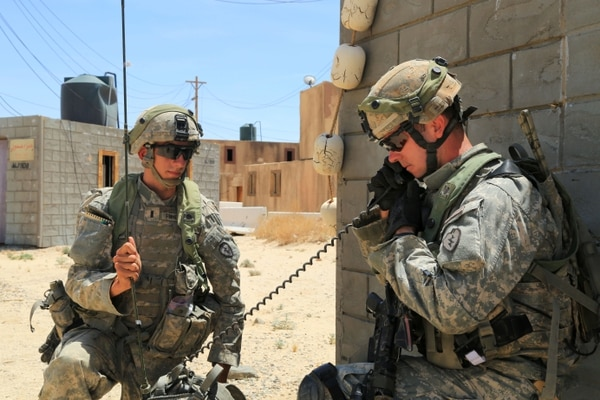 Soldiers use a radio to communicate at the National Training Center. The Army is doubling the amount of time recruits spend on radio and voice communication at basic training (Spc. Stephen Solomon/Army)