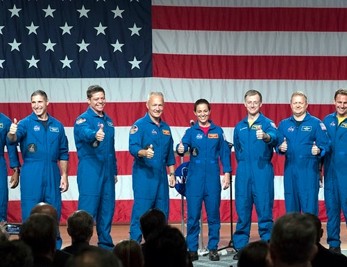 Astronauts, from left to right, Victor Glover, Michael Hopkins, Robert Behnken, Douglas Hurley, Nicole Mann, Christopher Ferguson, Eric Boe, Josh Cassada and Sunita Williams give a thumbs up to the crowd after NASA announced them as astronauts assigned to crew the first flight tests and missions of the Boeing CST-100 Starliner and SpaceX Crew Dragon, Friday, Aug. 3, 2018, in Houston. The astronauts will ride the first commercial capsules into orbit next year and return human launches to the U.S. (David J. Phillip/AP)