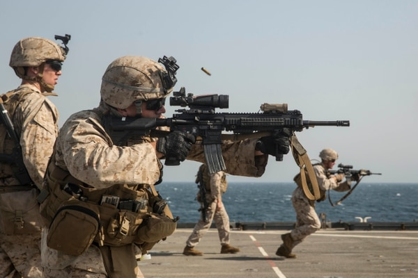 A U.S. Marine fires at his target on the move during a short-range marksmanship qualification course aboard the dock landing ship USS Rushmore (LSD 47). (Sgt. Emmanuel Ramos/Marine Corps)