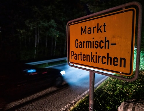 In this Sept. 13, 2020 taken photo a car drives past the place name sign in Garmisch-Partenkirchen, Germany. (Lino Mirgeler/dpa via AP)