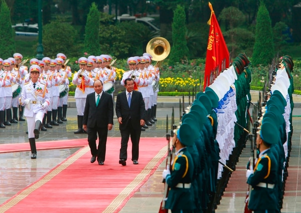 Cambodian Prime Minister Hun Sen, center right, and his Vietnamese counterpart Nguyen Xuan Phuc, center left, review an honor guard in Hanoi on Friday. (Tran Van Minh/AP)