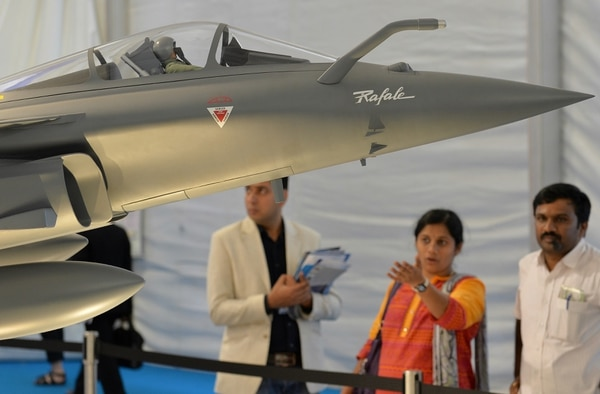 Visitors look at a scale model of a Dassault Rafael multi-role combat fighter at a stall during the Aero India 2015 air show at Yelahanka Airforce Station in Bangalore on February 20, 2015. AFP PHOTO / Manjunath KIRAN (Photo credit should read MANJUNATH KIRAN/AFP/Getty Images)