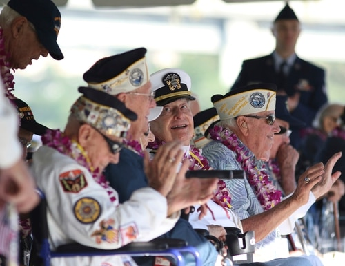 Pearl Harbor survivor Lou Conter, 98, center, who was the only survivor from the USS Arizona to make it to this year's ceremony, smiles during the 78th anniversary of the Japanese attack on Pearl Harbor, Saturday. (Caleb Jones/AP)