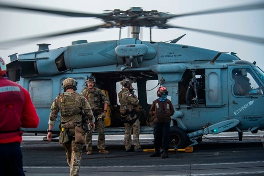 Sailors assigned to an EOD unit board an MH-60S Seahawk helicopter on the flight deck of aircraft carrier USS Ronald Reagan to head to an oil tanker that was attacked off the coast of Oman in the Arabian Sea on Friday, July 30, 2021. (Quinton A. Lee/U.S. Navy, via AP)