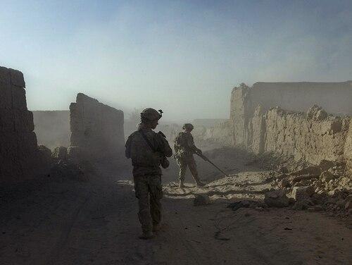 Soldiers walk behind operators of mine-detecting devices at Naja-bien village, Panjwai district, Afghanistan. (Tony Karumba/AFP/GettyImages)