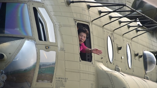 A visitor shows her face out of the window of a US Army CH-47 Chinook helicopter during a media preview day of the Seoul International Aerospace and Defense Exhibition near Seoul in 2015. (Jung Yeon-Je/AFP via Getty Images)