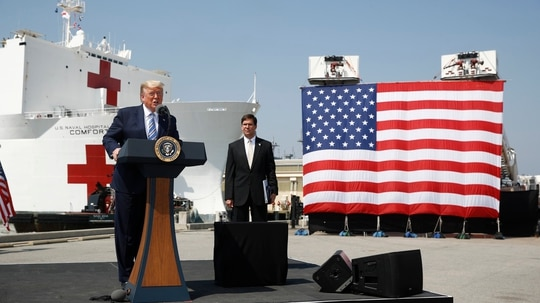 President Donald Trump speaks in front of the USNS Comfort at Naval Station Norfolk in Norfolk, Va., on March 28, 2020, before it traveled to New York to assist with coronavirus response efforts. With him is Defense Secretary Mark Esper. (Patrick Semansky/AP)