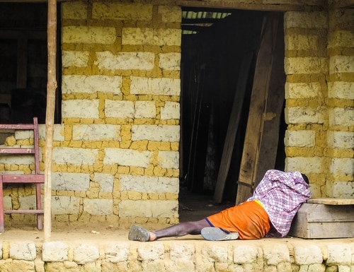 FILE - In this Tuesday, Oct. 21, 2014 file photo, a man suffering from the Ebola virus lies on the floor outside a house in Port Loko Community, situated on the outskirts of Freetown, in Sierra Leone. Professors from three leading British universities say policies favoring international debt repayment over social spending contributed to the Ebola crisis by hampering health care in the three worst-hit West African countries. Conditions for loans from the International Monetary Fund prevented an effective response to the outbreak that has killed nearly 8,000 people, the academics allege in a report in The Lancet Global Health journal this month. (AP Photo/Michael Duff, File)