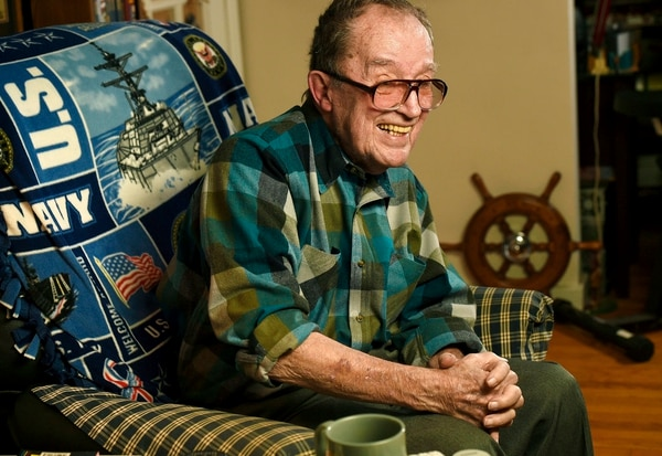 In this November 2014 file photo, Lawrence J. Reilly Sr., a U.S. Navy veteran of World War ll and the Vietnam War, sits in the living room of his home in Syracuse, N.Y. Reilly, a U.S. Navy veteran who survived the 1969 ship collision that claimed the life of his son and later fought unsuccessfully to have the victims' names inscribed on the Vietnam Veterans Memorial has died. His daughter says he died Wednesday, May 23, 2018, at a Syracuse hospital from complications from pneumonia. He was 93. (Mike Greenlar /The Syracuse Newspapers via AP, File)